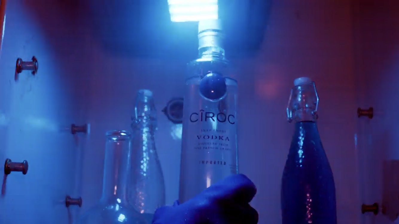 hand grabbing ciroc vodka bottle out of freezer with blue lighting