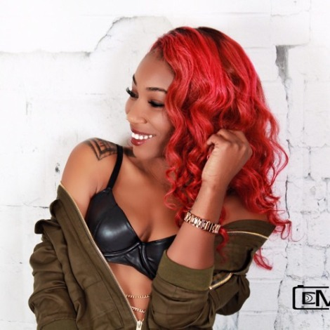black female singer with red hair black bra and olive green jacket