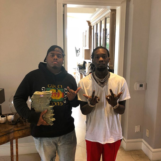 two rappers Duke Deuce and Offset holding a stack of money and throwing finger signs