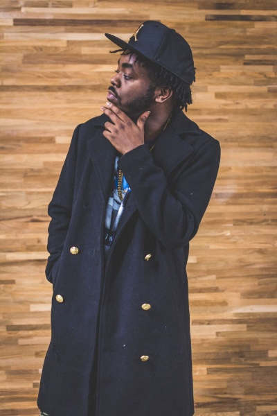 black male rapper dressed in long black trench coat with black hat and gold chain